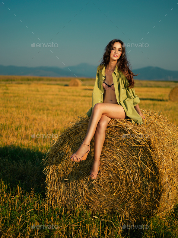 beautiful woman sitting on hay stack - Stock Photo - Images