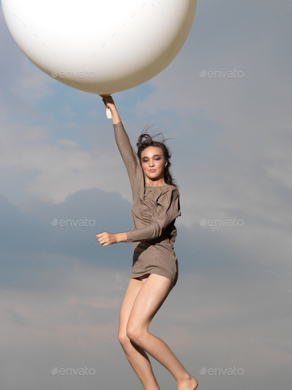 happy woman jumping with big, white balloon - Stock Photo - Images