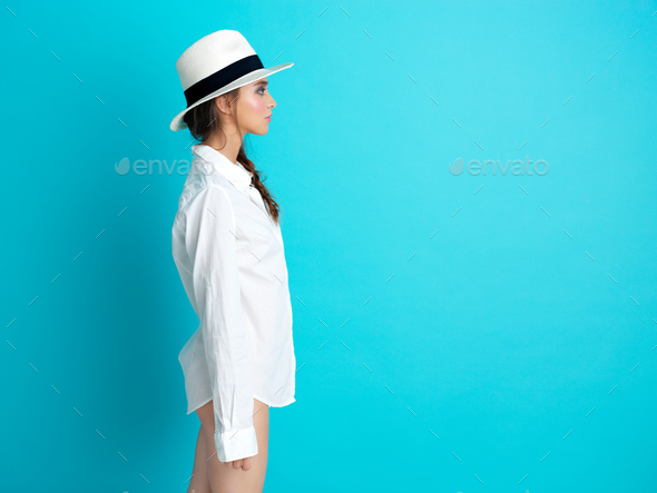 young woman blue background white hat, shirt - Stock Photo - Images