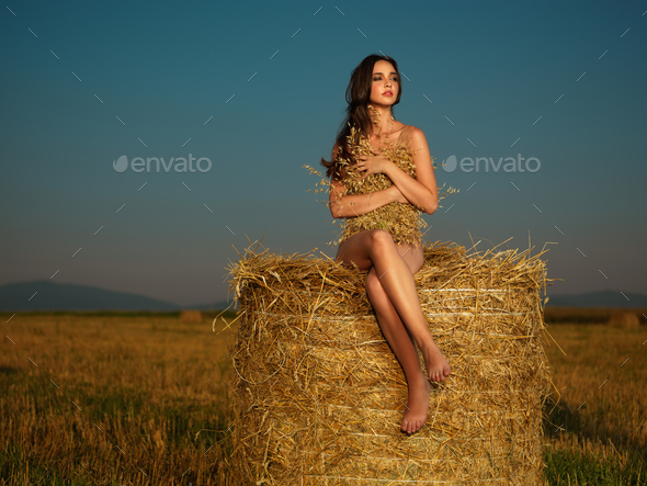young woman watching sunset on hay stack - Stock Photo - Images