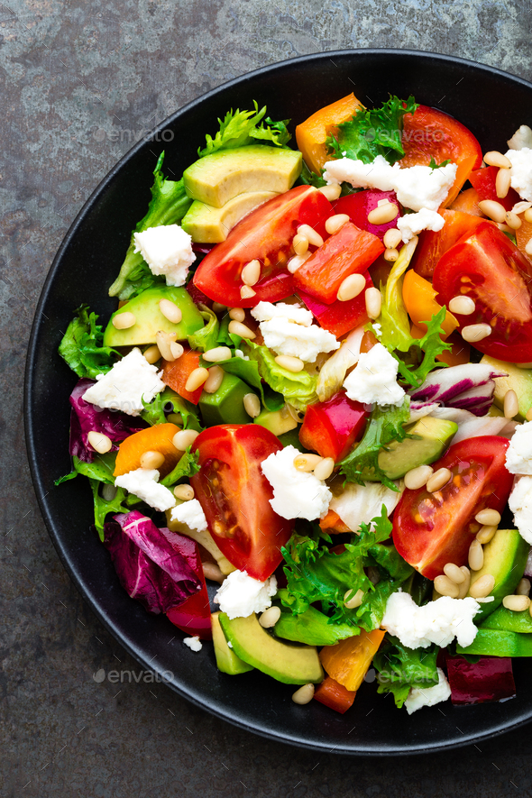 Vegetable dish, salad with avocado, pepper, tomato, italian mix, fresh lettuce, feta cheese - Stock Photo - Images