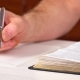 Man Is Holding a Pen in His Hand with an Open Book Lying in Fornt of Him - VideoHive Item for Sale