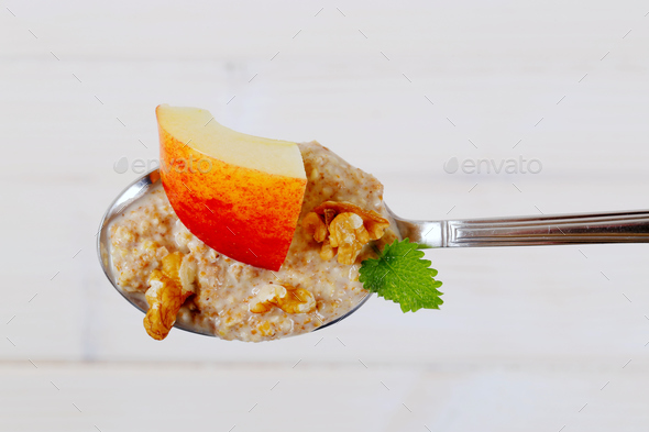 spoon of oatmeal porridge with apples and walnuts - Stock Photo - Images