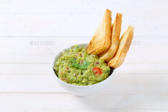 bowl of guacamole with toast - Stock Photo - Images
