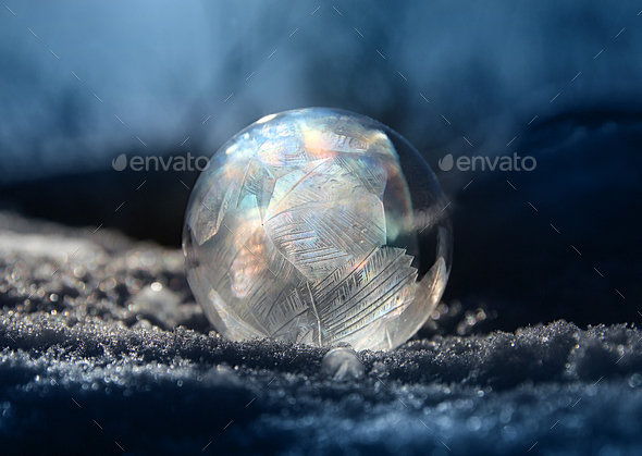 Frozen soap bubble ball on winter snow - Stock Photo - Images