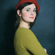 woman in green dress and red beret on the black wall background - PhotoDune Item for Sale