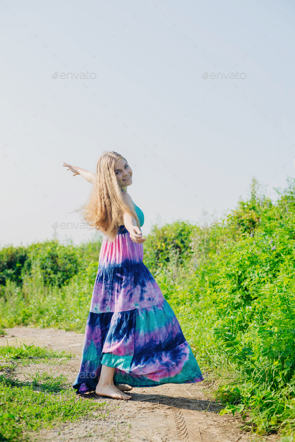 white caucasian blonde girl with colorful long dress - Stock Photo - Images