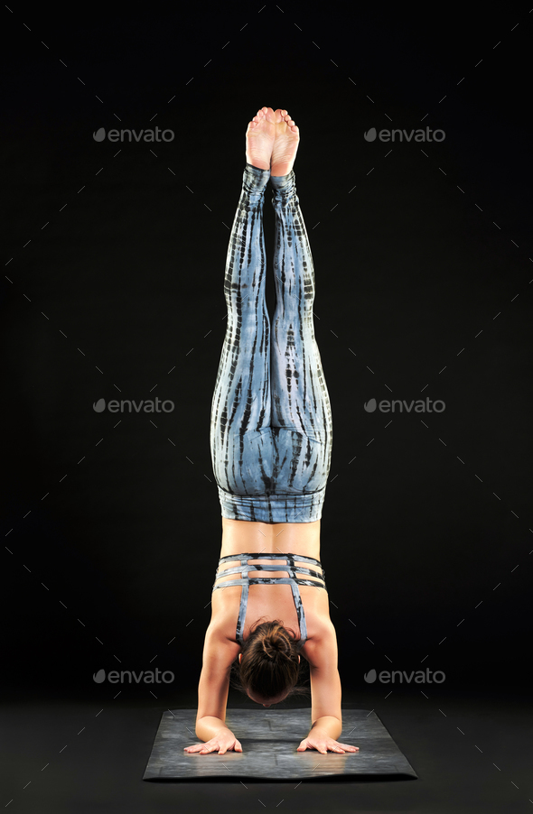 Woman demonstrating a forearm stand or pincha pose - Stock Photo - Images