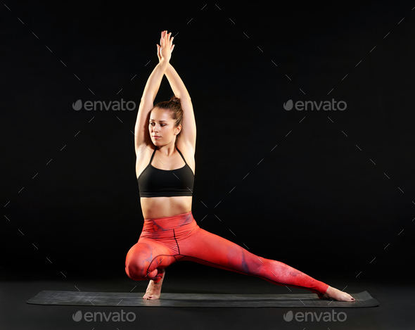Fit woman doing a side lunge pose in yoga - Stock Photo - Images