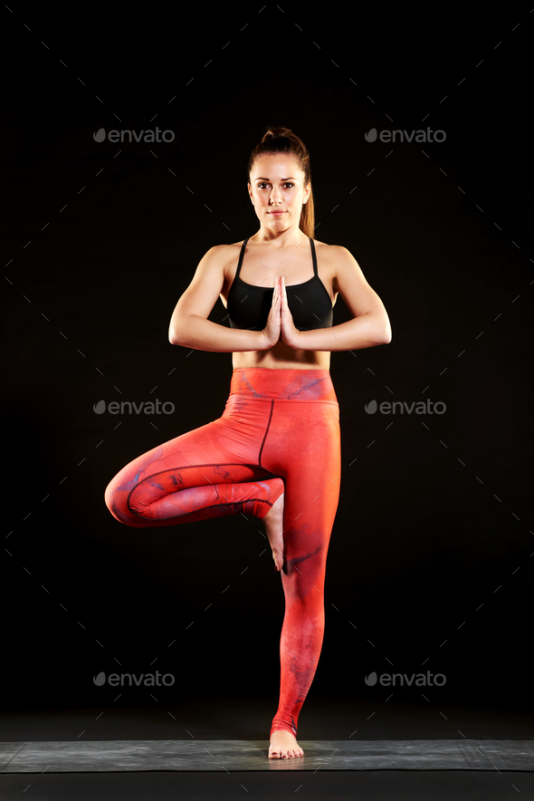 Woman practicing balance control in the tree pose - Stock Photo - Images