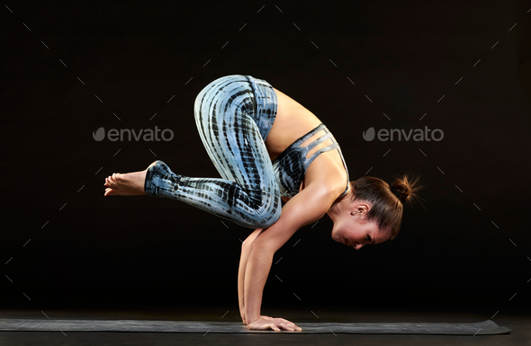 Woman demonstrating a crow pose in yoga - Stock Photo - Images