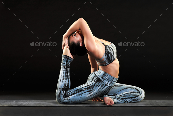 Supple fit woman doing a king pigeon yoga pose - Stock Photo - Images
