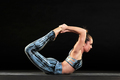 Athletic woman demonstrating the bow pose in yoga - PhotoDune Item for Sale