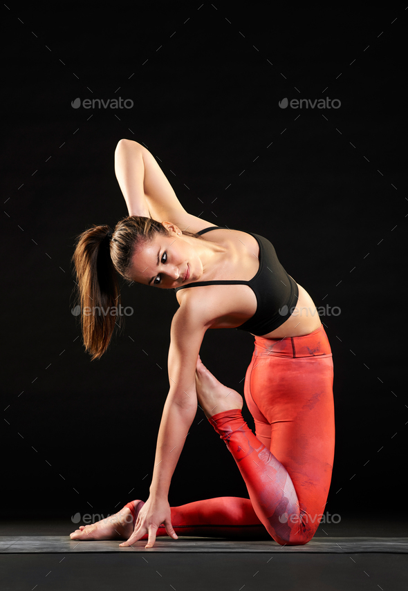 Muscular fit woman doing a camel pose variation - Stock Photo - Images