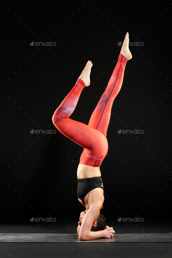 Woman working out on a yoga mat doing a headstand - Stock Photo - Images