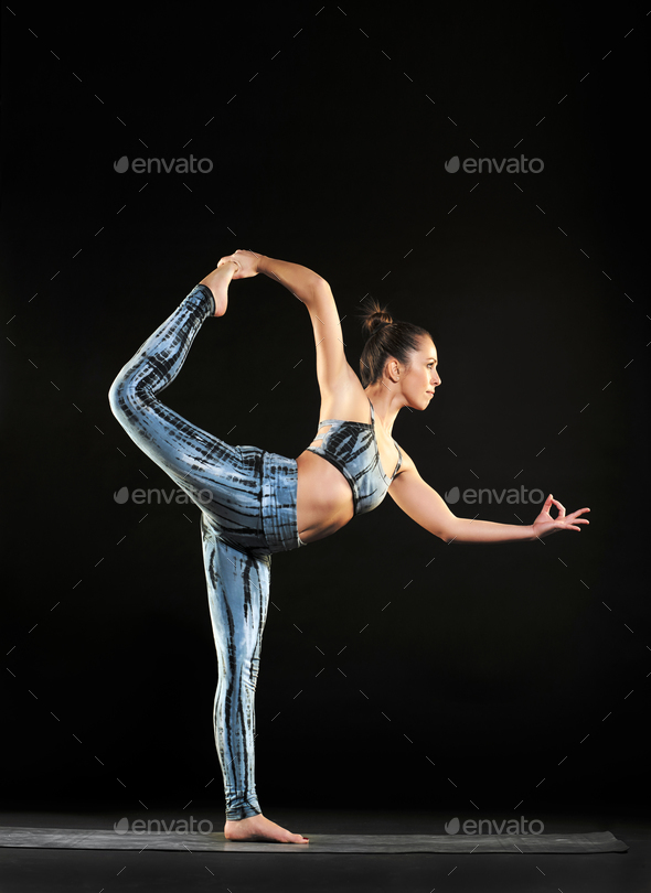 Woman doing a dancer pose during a yoga workout - Stock Photo - Images
