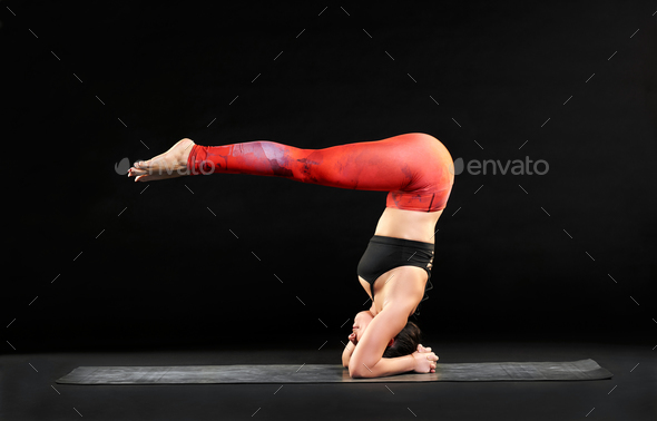 Muscular woman doing a headstand with pike legs - Stock Photo - Images