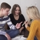 Teenage Friends Sitting on Bed Looking at Smartphone and Discussing