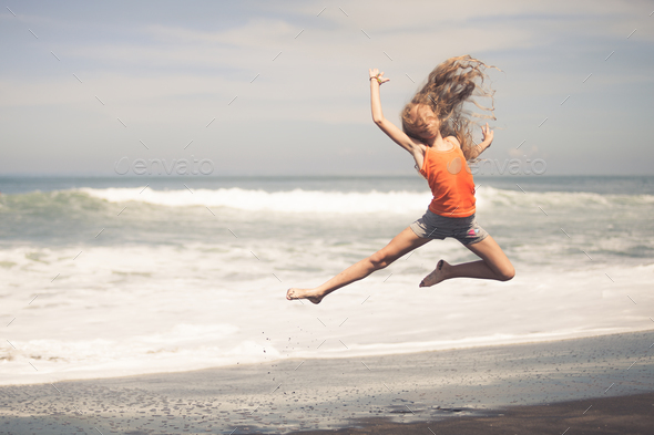 teen girl jumping on the beach at blue sea shore - Stock Photo - Images