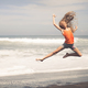 teen girl jumping on the beach at blue sea shore - PhotoDune Item for Sale