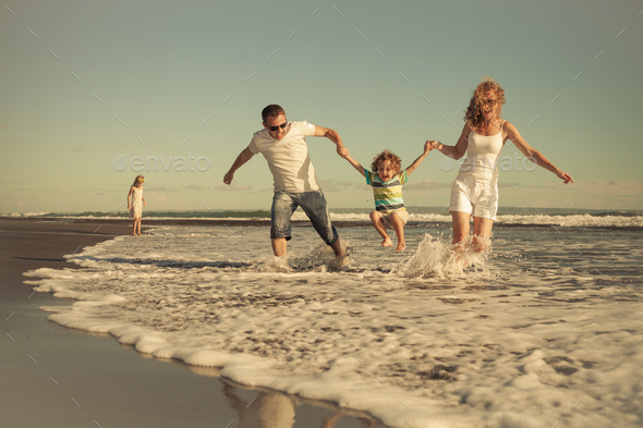 Happy family walking on the beach at the day time. - Stock Photo - Images