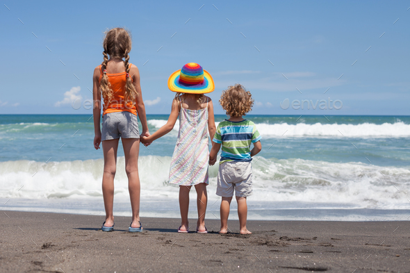 Three happy children playing on the beach at the day time - Stock Photo - Images