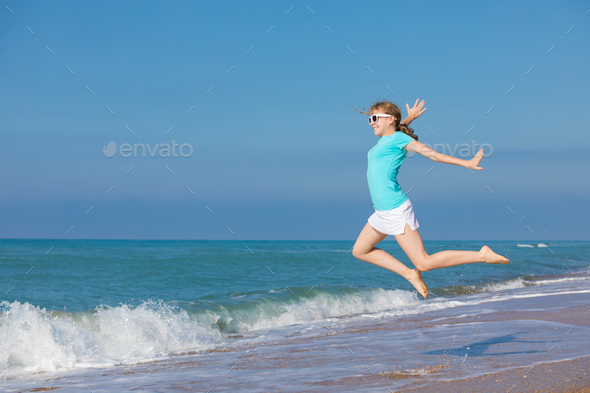 teen girl jumping on the beach at blue sea shore in summer vacat - Stock Photo - Images