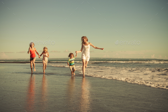 Mother and children running on the beach. - Stock Photo - Images