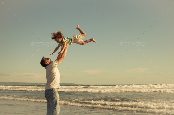 Father and son playing on the beach at the day time. Concept of - Stock Photo - Images