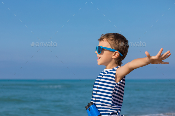 One happy little boy playing on the beach at the day time - Stock Photo - Images