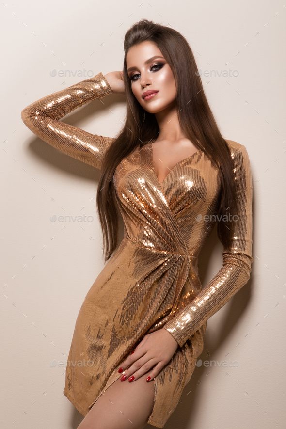 Beautiful woman with professional make up. Gold dress - Stock Photo - Images