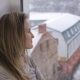 Dreaming Girl Looking Through the Window on Snowfall - VideoHive Item for Sale