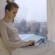 Beautiful Woman Typing on Her Laptop and Sitting on Windowsill - VideoHive Item for Sale