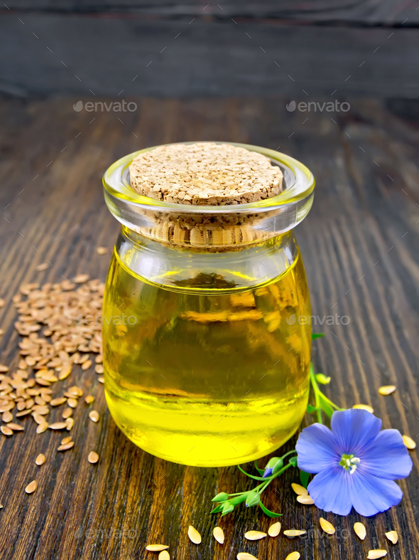 Oil linenseed with flower on board - Stock Photo - Images