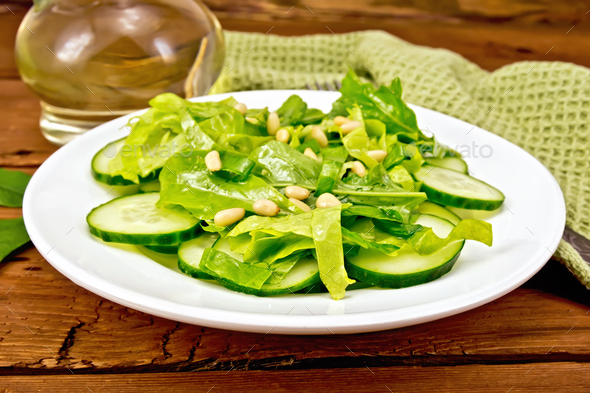 Salad from spinach and cucumber with napkin on board - Stock Photo - Images