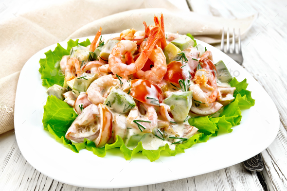 Salad with shrimp and tomato in plate on light board - Stock Photo - Images