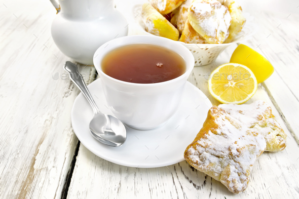 Tea in white cup with lemon cookies on board - Stock Photo - Images