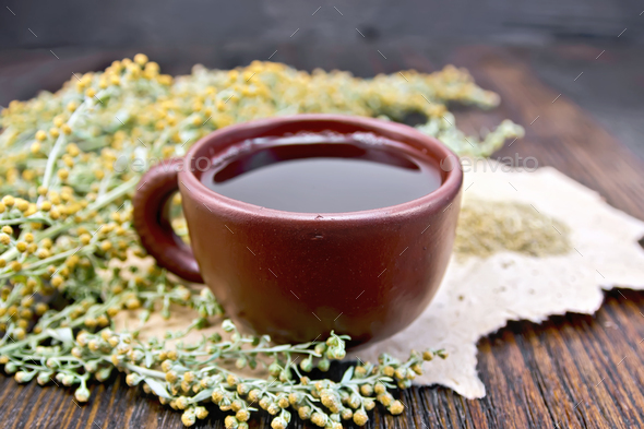 Tea with wormwood in clay cup on board - Stock Photo - Images