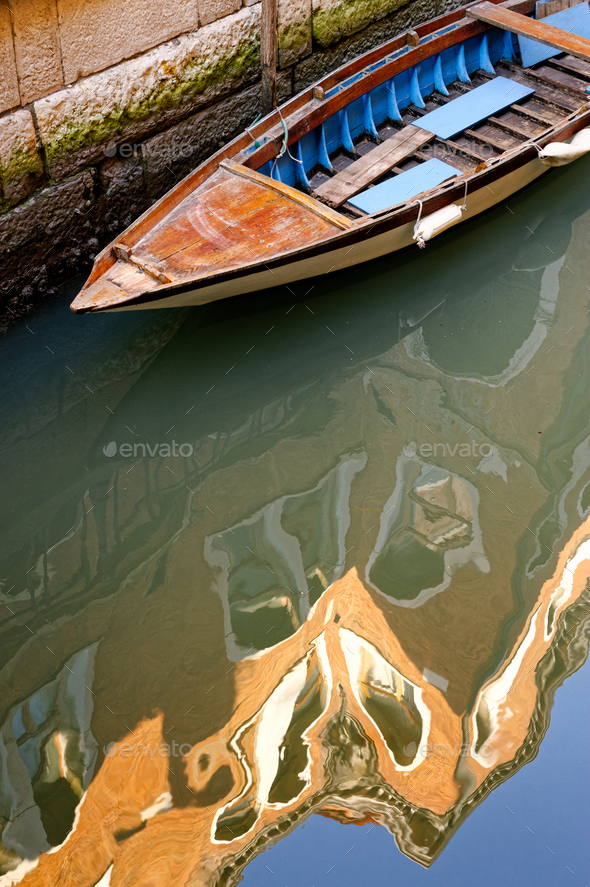 Old boat and old building reflection in water of venetian channel - Stock Photo - Images
