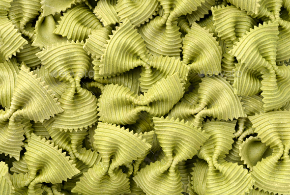 Uncooked green spinach farfalle pasta background - Stock Photo - Images