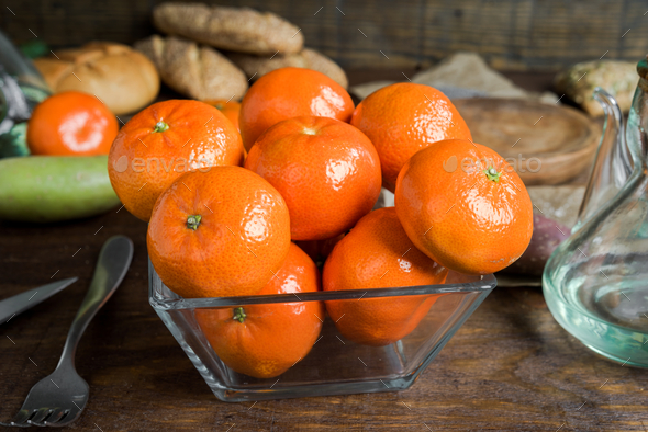 group of tangerines in glass bowl on classic rustic wood - Stock Photo - Images