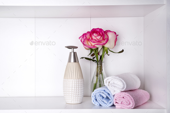Stack of towels with a soap dispenser and roses in vasein a bathroom closeup - Stock Photo - Images