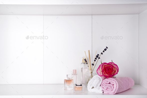 Stack of bath towels with rose and parfums on light background - Stock Photo - Images