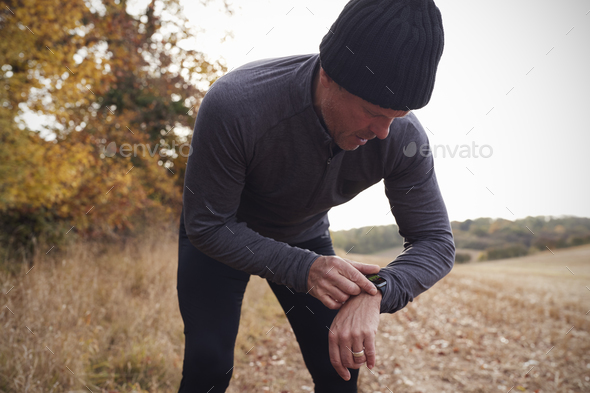 Mature Man On Autumn Run Around Field Checks Activity Tracker - Stock Photo - Images