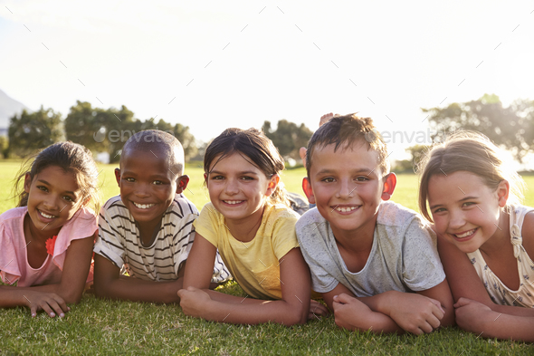 Boys and girls lying on grass in Summer, looking to camera - Stock Photo - Images