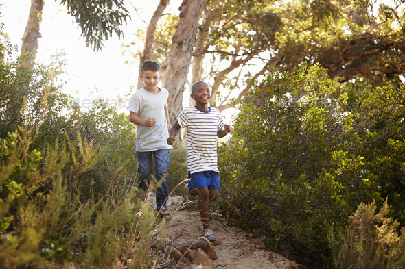 Two smiling young boys running down a forest path - Stock Photo - Images
