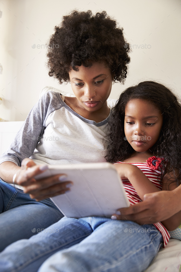 Mother And Daughter Siting On Bed Using Digital Tablet - Stock Photo - Images