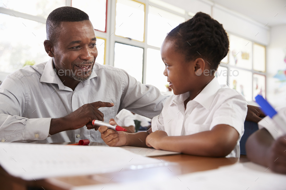 Teacher helping elementary school girl at her desk, close up - Stock Photo - Images