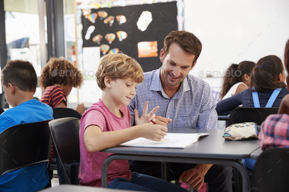 Teacher and young school boy looking at notebook in class - Stock Photo - Images