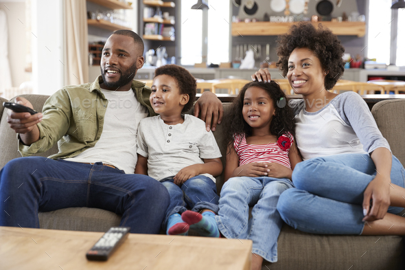Family Sitting On Sofa In Open Plan Lounge Watching Television - Stock Photo - Images